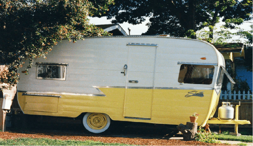 a small travel trailer parked outside home