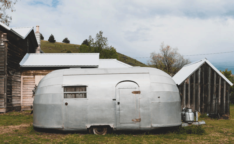 an old airstream trailer parked in front of house
