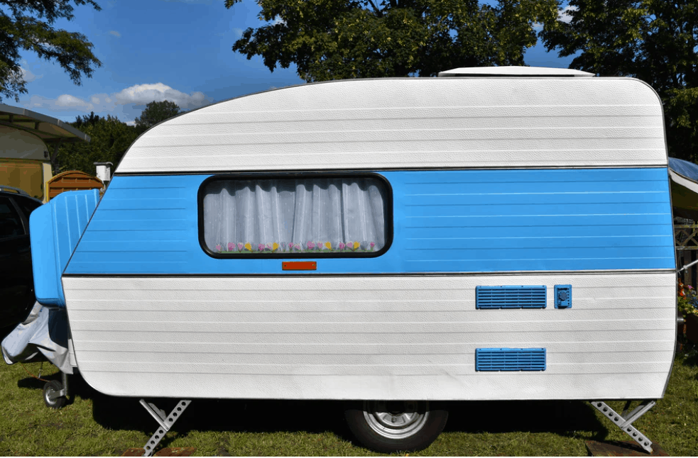 a small travel trailer parked outside a house