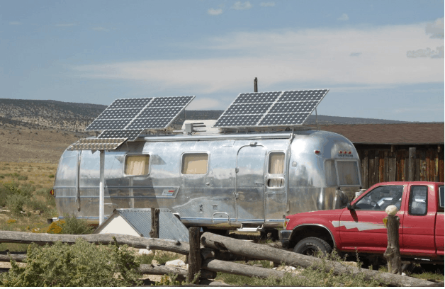 an airstream trailer with solar panels mounted on roof